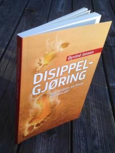 """En bok som står oppreist på gamle treplanker. Bokens forside er av dype fotspor i sand, det ryker og gløder fra fotsporene. Tittelen på boken er """"Disippelgjøring"""" av Øyvind jansen. Undertittelen er: """"Gjør disipler, sa Jesus. Hvordan da?"""""""